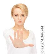 Купить «Недовольная молодая женщина выставила руку вперед в жесте стоп», фото № 4344744, снято 12 февраля 2011 г. (c) Syda Productions / Фотобанк Лори