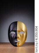 Купить «Золотисто-чёрная театральная маска на столе», фото № 4350904, снято 17 декабря 2012 г. (c) Elnur / Фотобанк Лори