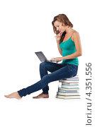 Купить «Студентка сидит на стопке книг с ноутбуком», фото № 4351556, снято 22 августа 2012 г. (c) Elnur / Фотобанк Лори