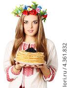Купить «Девушка в венке из цветов и вышиванке держит блины с черной икрой на белом фоне», фото № 4361832, снято 11 февраля 2013 г. (c) Юлия Маливанчук / Фотобанк Лори