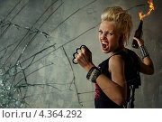 Кричащая девушка с кастетом держит в руке бутылку с горящей смесью и смотрит в камеру. Стоковое фото, фотограф Andrejs Pidjass / Фотобанк Лори