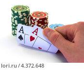 Игра в покер - рука держит игральные карты, рядом фишки. Стоковое фото, фотограф Михаил Балберов / Фотобанк Лори