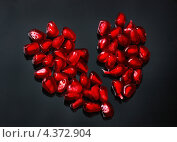 Красное сердце из семян граната на сером фоне. Стоковое фото, фотограф Александра Ткачук / Фотобанк Лори