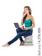 Купить «Мечтательная выпускница с ноутбуком, сидя на стопке книг», фото № 4378496, снято 22 августа 2012 г. (c) Elnur / Фотобанк Лори