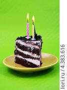 Кусок торта с двумя свечами на тарелке. Стоковое фото, фотограф CHERKAUSKAS VIKTOR / Фотобанк Лори