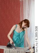 Молодая женщина гладит белье и разговаривает по телефону. Стоковое фото, фотограф Виталий Верхозин / Фотобанк Лори