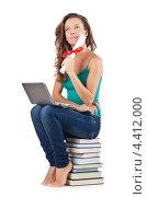 Купить «Студентка с ноутбуком сидит на стопке книг», фото № 4412000, снято 22 августа 2012 г. (c) Elnur / Фотобанк Лори
