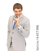 Купить «Привлекательный молодой человек в сорочке и светлом костюме с пальцем у губ», фото № 4417996, снято 8 апреля 2012 г. (c) Syda Productions / Фотобанк Лори