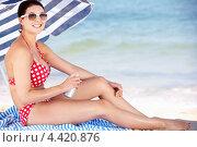 Купить «Девушка сидит у моря под зонтиком, нанося крем на кожу», фото № 4420876, снято 16 июля 2012 г. (c) Monkey Business Images / Фотобанк Лори