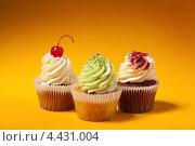 Купить «Три вкусных кекса на оранжевом фоне», фото № 4431004, снято 12 марта 2013 г. (c) Максим Бондарчук / Фотобанк Лори