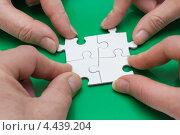 Четыре руки собирают пазл. Стоковое фото, фотограф Владимир Никифоров / Фотобанк Лори