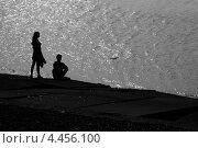 Силуэт молодого мужчины и женщины на берегу на фоне волн (2008 год). Стоковое фото, фотограф Мария Сударикова / Фотобанк Лори