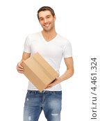 Купить «Привлекательный молодой человек в джинсах с посылкой в руке», фото № 4461324, снято 8 апреля 2012 г. (c) Syda Productions / Фотобанк Лори