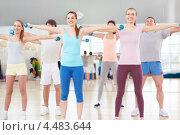 Купить «Молодые люди с гантелями в руках занимаются в зале фитнес-клуба», фото № 4483644, снято 31 января 2013 г. (c) Raev Denis / Фотобанк Лори