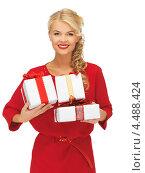 Купить «Счастливая девушка в красном платье с подарками в руках», фото № 4488424, снято 7 октября 2012 г. (c) Syda Productions / Фотобанк Лори