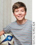 Купить «Весёлый мальчик-подросток с футбольным мячом в руках», эксклюзивное фото № 4492424, снято 7 апреля 2013 г. (c) Игорь Низов / Фотобанк Лори