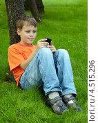 Купить «Мальчик сидит на траве под деревом с мобильным телефоном», фото № 4515296, снято 18 июля 2011 г. (c) Losevsky Pavel / Фотобанк Лори
