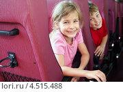 Купить «Улыбающиеся мальчик и девочка в креслах туристического автобуса», фото № 4515488, снято 19 июля 2011 г. (c) Losevsky Pavel / Фотобанк Лори