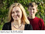 Купить «Улыбающаяся светловолосая девушка на фоне мужчины на природе», фото № 4515832, снято 30 октября 2011 г. (c) Losevsky Pavel / Фотобанк Лори