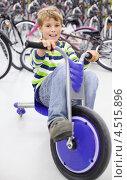 Купить «Счастливый мальчик на трехколесном велосипеде в магазине», фото № 4515896, снято 10 сентября 2011 г. (c) Losevsky Pavel / Фотобанк Лори