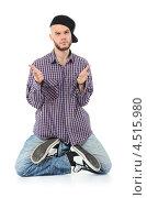 Мужчина реппер в молодежной одежде стоит на коленях на белом фоне. Стоковое фото, фотограф Losevsky Pavel / Фотобанк Лори