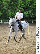 Купить «Жокей в очках и белой рубашке  едет на лошади на ипподроме», фото № 4516520, снято 10 июня 2011 г. (c) Losevsky Pavel / Фотобанк Лори