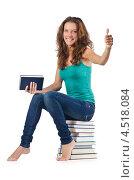 Купить «Студентка сидит на стопке книг показывает одобрительный жест», фото № 4518084, снято 22 августа 2012 г. (c) Elnur / Фотобанк Лори
