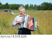 Веселый пожилой мужчина играет на гармошке в поле, фото № 4518628, снято 5 июля 2011 г. (c) Losevsky Pavel / Фотобанк Лори