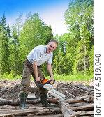 Купить «Довольный дачник с бензопилой на даче пилит дрова», фото № 4519040, снято 29 мая 2010 г. (c) Куликов Константин / Фотобанк Лори