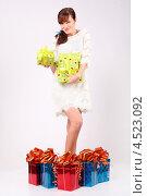 Купить «Довольная молодая женщина в коротком платье с подарками», фото № 4523092, снято 16 декабря 2011 г. (c) Losevsky Pavel / Фотобанк Лори
