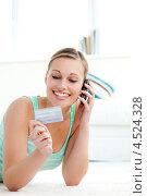 Девушка с улыбкой смотрит на кредитную карту. Стоковое фото, агентство Wavebreak Media / Фотобанк Лори