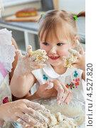 Купить «Маленькая девочка с руками, измазанными тестом, готовит на кухне вместе с мамой», фото № 4527820, снято 4 июня 2010 г. (c) Wavebreak Media / Фотобанк Лори