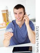 Молодой человек звонит по телефону, глядя на свою банковскую карту. Стоковое фото, агентство Wavebreak Media / Фотобанк Лори