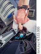 Юная девушка лежит на краю небоскреба на фоне бассейна далеко внизу (2013 год). Стоковое фото, фотограф Игорь Романчук / Фотобанк Лори