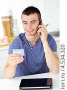 Парень смотрит на кредитную карту и разговаривает по телефону. Стоковое фото, агентство Wavebreak Media / Фотобанк Лори