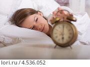 Девушка в постели выключает будильник. Стоковое фото, фотограф Дегтярева Виктория / Фотобанк Лори