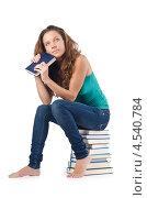 Купить «Задумавшаяся студентка сидит на стопке книг», фото № 4540784, снято 22 августа 2012 г. (c) Elnur / Фотобанк Лори