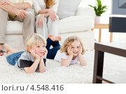 Купить «Дети смотрят телевизор лежа на полу. Родители сидят на диване», фото № 4548416, снято 26 октября 2010 г. (c) Wavebreak Media / Фотобанк Лори