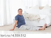 Пожилой мужчина делает зарядку возле кровати. Стоковое фото, агентство Wavebreak Media / Фотобанк Лори