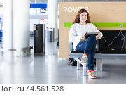 Купить «Девушка с планшетом в руках в зале ожидания аэропорта», фото № 4561528, снято 8 апреля 2013 г. (c) Кекяляйнен Андрей / Фотобанк Лори