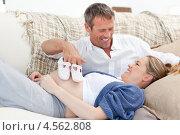 Купить «Мужчина и беременная жена играют на диване с детскими пинетками», фото № 4562808, снято 2 ноября 2010 г. (c) Wavebreak Media / Фотобанк Лори