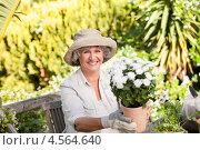 Счастливая пожилая женщина с горшечными цветами в летнем саду. Стоковое фото, агентство Wavebreak Media / Фотобанк Лори