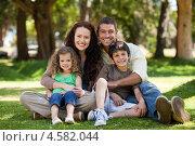 Купить «Счастливая семья сидит в парке на траве», фото № 4582044, снято 9 ноября 2010 г. (c) Wavebreak Media / Фотобанк Лори