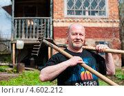 Купить «Счастливый мужчина с лопатой и граблями на плече на фоне дачи», эксклюзивное фото № 4602212, снято 5 мая 2013 г. (c) Игорь Низов / Фотобанк Лори