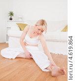 Привлекательная блондинка занимается дома на полу наклонами. Стоковое фото, агентство Wavebreak Media / Фотобанк Лори
