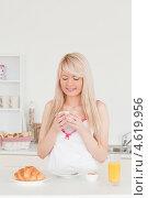 Блондинка смотрит на чашку кофе у себя в руках за завтраком, рядом стоит стакан сока. Стоковое фото, агентство Wavebreak Media / Фотобанк Лори