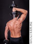 Купить «Бодибилдер в черной майке с гантелью в руках, вид со спины», фото № 4635952, снято 14 июля 2012 г. (c) Андрей Попов / Фотобанк Лори