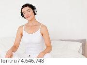 Купить «Женщина слушает музыку в наушниках сидя на кровати», фото № 4646748, снято 17 июня 2011 г. (c) Wavebreak Media / Фотобанк Лори