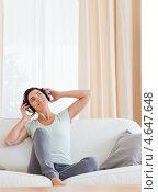 Купить «Улыбающаяся брюнетка наслаждается музыкой в наушниках сидя на диване в гостиной дома», фото № 4647648, снято 17 июня 2011 г. (c) Wavebreak Media / Фотобанк Лори