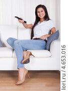 Купить «Улыбающаяся женщина переключает каналы на телевизоре пультом ДУ», фото № 4653016, снято 30 сентября 2012 г. (c) Андрей Попов / Фотобанк Лори